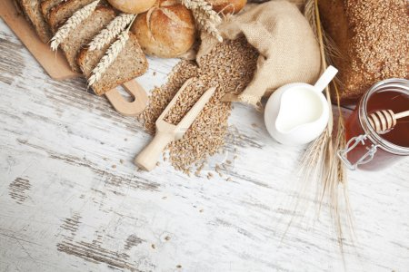 Rustic bread and wheat on an old vintage planked wood table. background with free text space