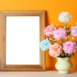 Wooden picture frame on orange wall with flowers...