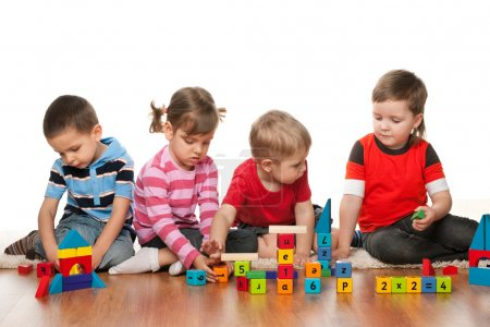 Photo for Four children are playing on the floor with blocks - Royalty Free Image
