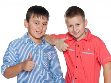 Two boys hold their thumbs up