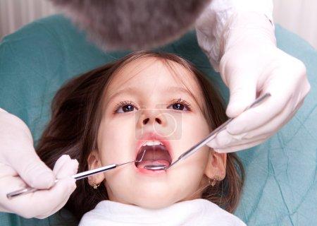 Photo pour Chez le dentiste - petite fille ont examen dentaire - image libre de droit