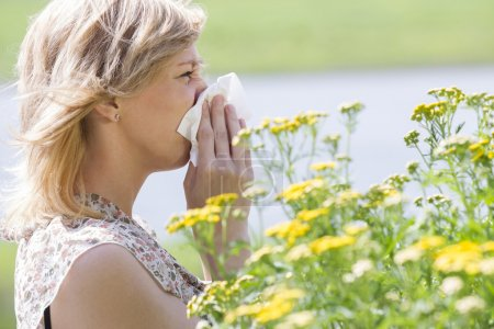 Woman blowing nose into tissue in front of flowers