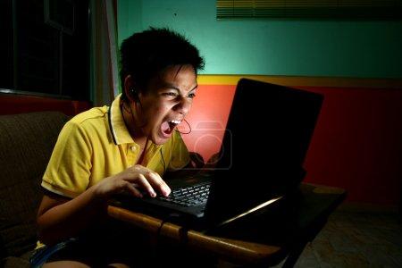 """Foto de Foto de una """"t"""" asiático, intensamente jugando o trabajando en un ordenador portátil - Imagen libre de derechos"""
