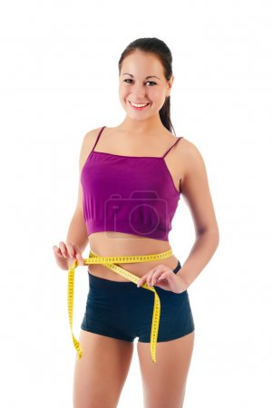 Smiling young woman holding a measure tape around her waist