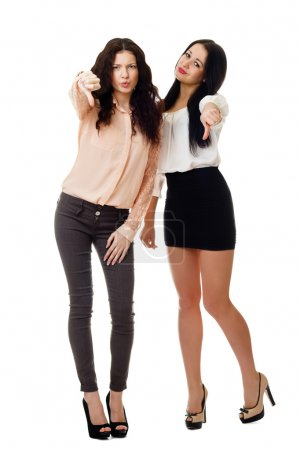 Two women standing and showing dislike gesture