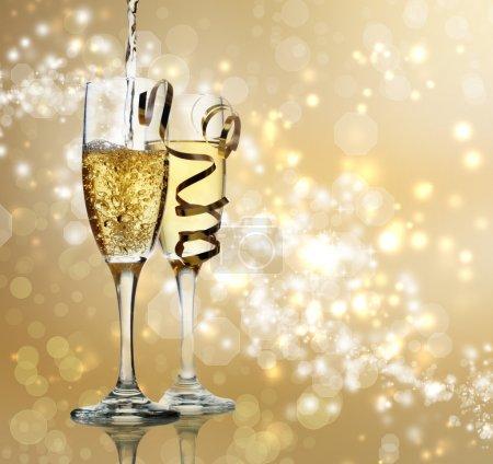 Photo pour Deux flûtes à champagne sur fond doré brillant - image libre de droit