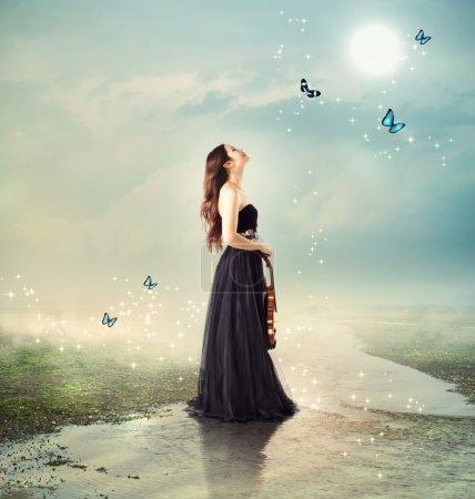 Foto de Violinist at a brook under the moon light (with butterflies) - Imagen libre de derechos