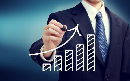 Photo for Businessman drawing a rising arrow over the bar graph - Royalty Free Image