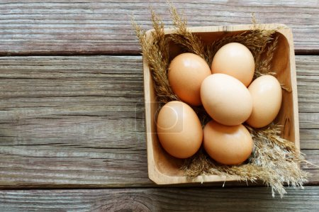 Photo for Fresh brown eggs on rustic wooden table - Royalty Free Image