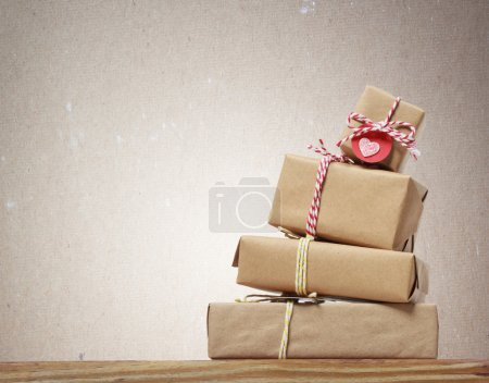 Photo for Stack of handcraft gift boxes on wooden board with a natural textured background - Royalty Free Image