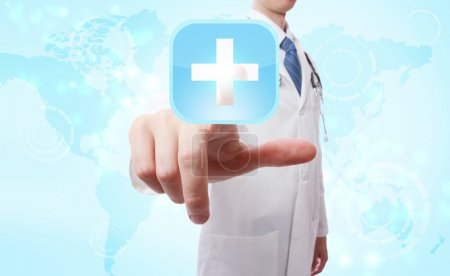 Photo for Medical Doctor pushing a blue cross icon over world map background - Royalty Free Image