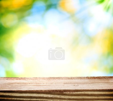Wooden table over shiny light background