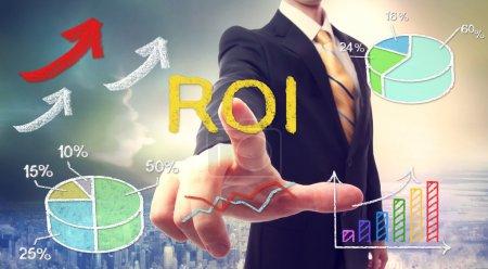 Photo pour Homme d'affaires touchant ROI (retour sur investissement) sur fond skyline - image libre de droit