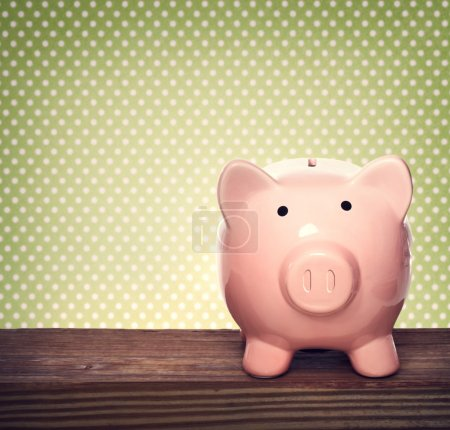 Photo for Pink piggy bank over green polka dots background - Royalty Free Image
