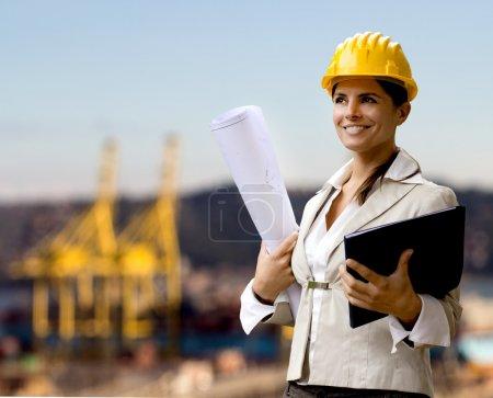 Photo pour Femme ingénieure navale avec casque et plans - image libre de droit