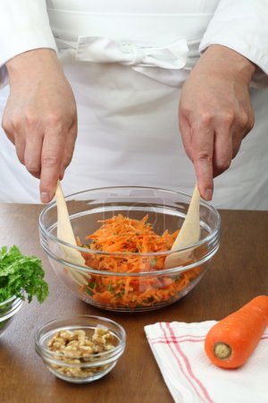 Photo for Making grated carrot salad(carottes rapees), tossing a salad - Royalty Free Image