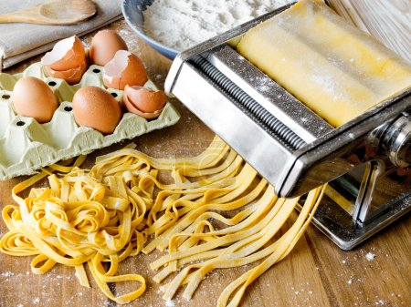 Photo for Fresh pasta cutting in machine. Fettuccini homemade. - Royalty Free Image