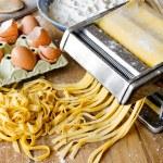 Fresh pasta cutting in machine. Fettuccini homemad...