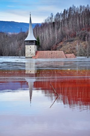 Abandoned church in the middle of a lake full with mining residu