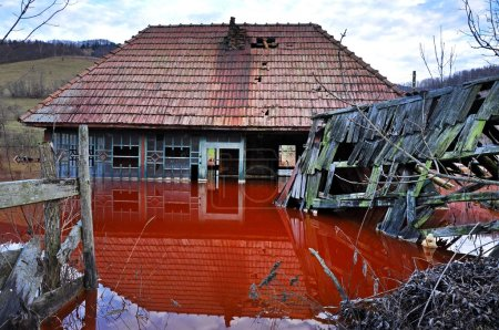 Ecological disaster. An abandoned village flooded by polluted wa