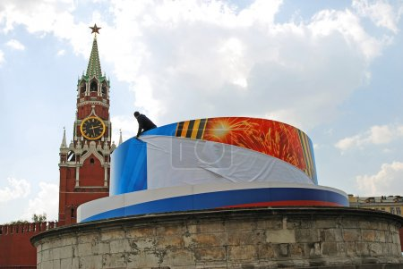 A worker fixes a holiday banner on the Red Square in Moscow.