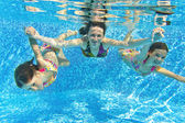 Happy smiling family underwater in swimming pool