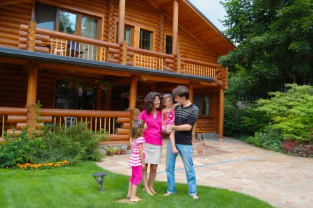 Happy smiling family near wooden house