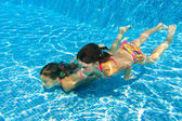 Kids swim underwater in pool