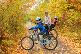 Happy family on bikes in autumn park
