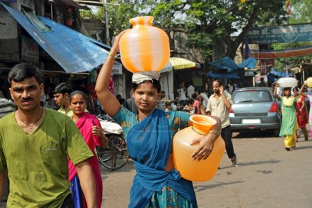 MUMBAI, INDIA - NOVEMBER 26: Indian woman carry water jugs in In