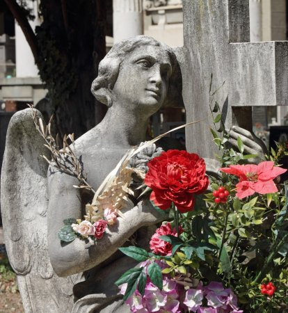 Angel statue with bouquet of flowers on tomb