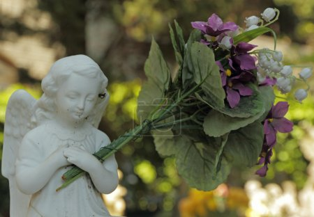 Little angel figure holding a huge bouquet of flowers