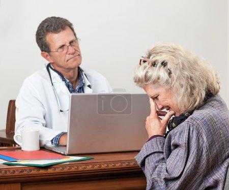 Photo pour Jolie mature femme consulte son médecin dans son bureau. Accent est mis sur la femme? face s. Elle a l'air inquiet et larmoyante. Le médecin a l'air ennuyé et impatiente. - image libre de droit