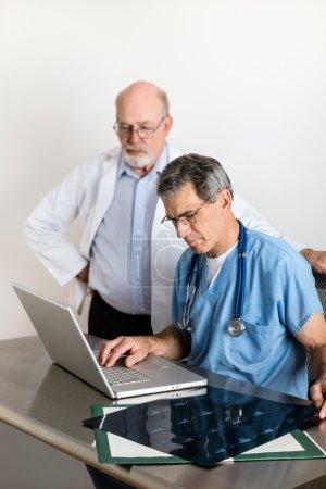 Senior Medical Doctors Discussing Patients MRI Film Scans
