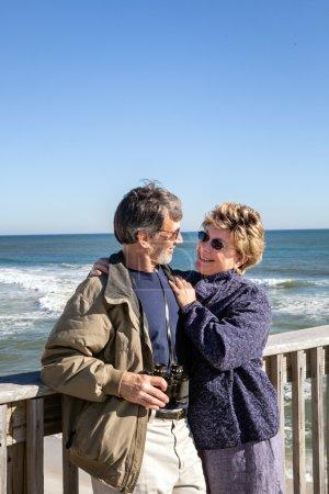 Retired senior couple hugging on sunny Florida fishing pier