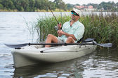 Man Fishing in Kayak in shallow reeds and grasses