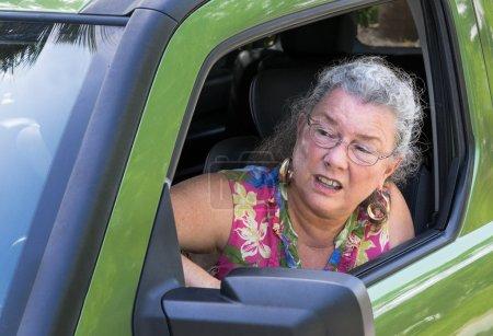 Photo pour Driver femme senior en colère avec rage au crier de fenêtre de la voiture. - image libre de droit