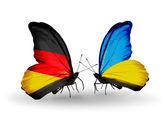 Dva motýli s příznaky na křídlech jako symbol vztahů, Německu a na Ukrajině