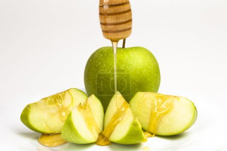 Green apple and honey isolated on white background...