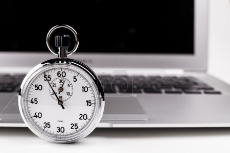Photo for Silver stopwatch with silver laptop in the background - Royalty Free Image
