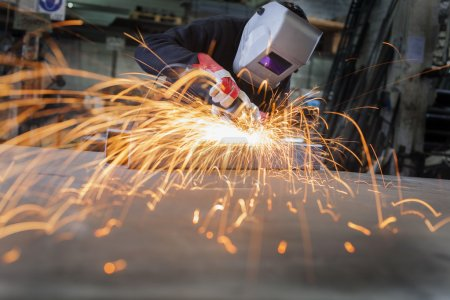 Photo for Metal wroker in a factory grinding with sparks - Royalty Free Image