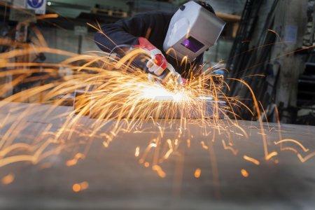 Photo pour Wroker métallique dans une usine de broyage avec des étincelles - image libre de droit