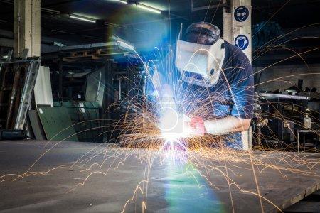Photo pour Soudage des travailleurs dans un atelier d'acier avec une lumière vive et des étincelles - image libre de droit
