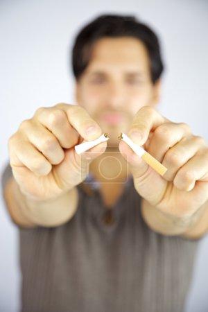 Man breaking cigarette stop smoking