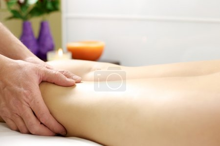 Photo for Hands of therapist doing massage to tired legs to get the stress out - Royalty Free Image