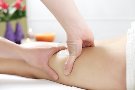 Strong hands working on legs to massage cellulite