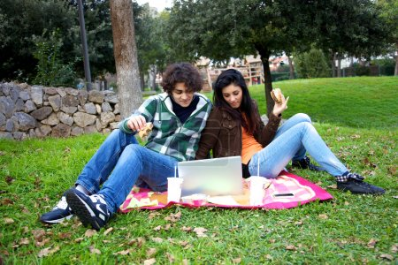 Happy couple watching pc while eating hamburger in park