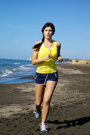 Strong woman listening music while running on the beach