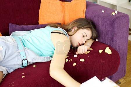 Sleepy teenager after having done mess with chips and pop corn