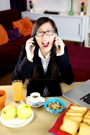 Screaming asian business woman with two phones stressed out